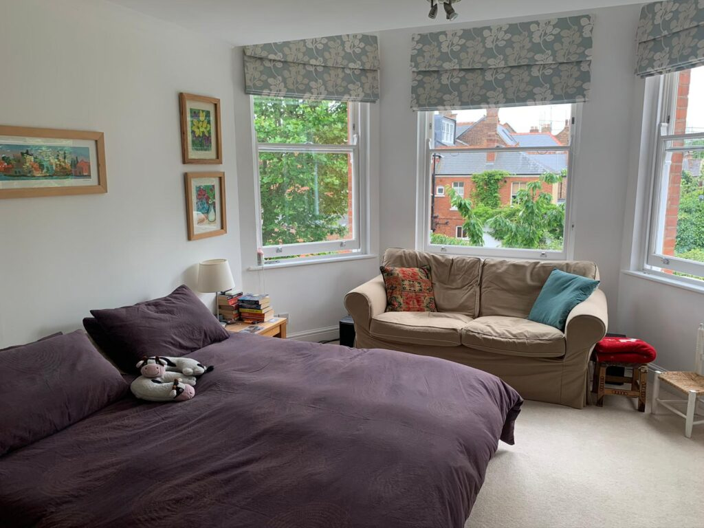 A bedroom with a large window Description automatically generated